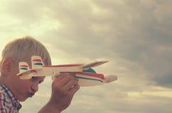 男孩用他的手跑飞机的模型入天空 免版税库存图片