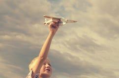 男孩用他的手跑飞机的模型入天空 免版税图库摄影
