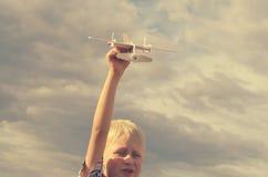 男孩用他的手跑飞机的模型入天空 库存图片