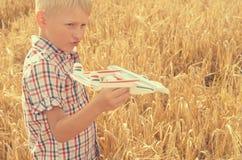 男孩用他的手跑飞机的模型入天空 图库摄影