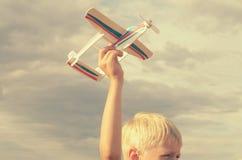 男孩用他的手跑飞机的模型入天空 库存照片