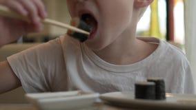 男孩白肤金发的讨债者滚动与在酱油的三文鱼 影视素材