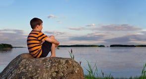 男孩的全景坐岩石在夏天晚上阳光下 免版税库存图片