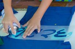 男孩的手有蓝色喷漆和模板信件的在一件蓝色T恤杉的希伯来语 免版税库存图片