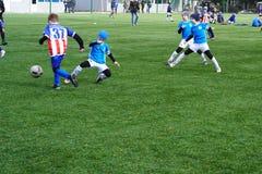 男孩的足球赛的场面 儿童` s在沥青的橄榄球队 儿童的橄榄球训练场 年轻 免版税库存图片