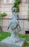 男孩的雕塑坐小桶 免版税库存图片