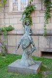 男孩的雕塑坐小桶 库存图片