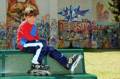 男孩直排轮式溜冰鞋滑冰 免版税图库摄影