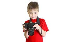 男孩看在照相机的照片 库存照片
