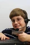 男孩看板卡使用年轻人的计算机赊帐 免版税库存照片