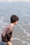 男孩看看海滨波浪 库存照片