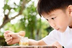 男孩看看蜂蜜梳子 库存照片