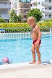 男孩看起来他的姐妹潜水入水 图库摄影
