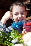 男孩着色愉快的复活节彩蛋 免版税库存照片
