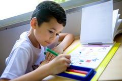 男孩着色执行大字书写他的家庭作业&# 免版税库存照片