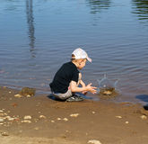 男孩石头投掷水 免版税库存图片