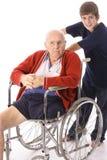 男孩祖父极大的推进的轮椅年轻人 库存图片