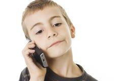 男孩移动电话告诉的年轻人 免版税库存照片