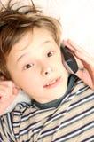男孩移动电话联系青少年 免版税库存图片
