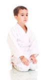 男孩空手道和服坐的白色 免版税库存图片