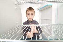 男孩空的冰箱 免版税库存照片