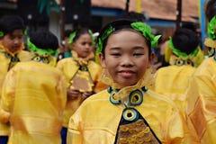 男孩穿的华丽椰子服装,他们在街道上跳舞 免版税库存图片