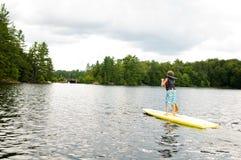 年轻男孩站立桨搭乘 免版税库存照片