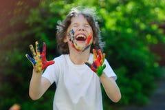 男孩笑、他的面孔和手在油漆 免版税库存照片