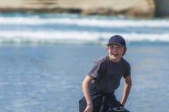 男孩笑和获得乐趣在海滩 库存照片