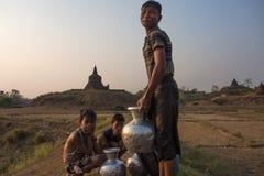 男孩等待运载水罐有寺庙的后面家作为背景 免版税库存照片