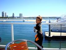 男孩等待他的在英属黄金海岸的游艇巡航 澳洲 免版税图库摄影