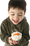 男孩红萝卜杯形蛋糕吃 库存图片