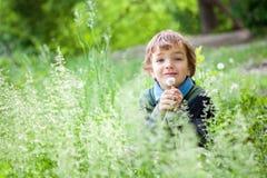 男孩纵向坐草在公园 图库摄影