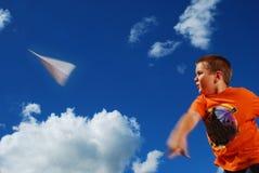 男孩纸飞机投掷的年轻人 免版税库存照片