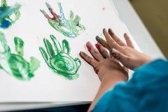 男孩绘画用他的做五颜六色的棕榈的手打印 免版税图库摄影