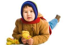 男孩给冬天穿衣 库存照片