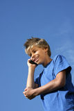 男孩给微笑打电话的移动电话 免版税库存照片