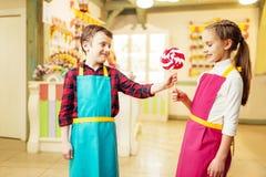 男孩给手工制造棒棒糖他的女朋友 库存照片