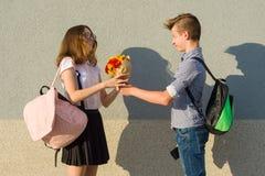 男孩给花女孩花束  夫妇少年室外画象  库存图片