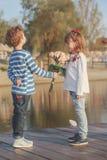 男孩给花女孩花束  图库摄影