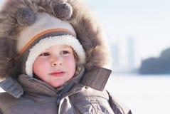 男孩给逗人喜爱的冬天穿衣 免版税库存图片