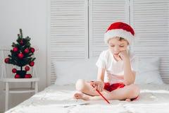 男孩考虑信件对圣诞老人 库存图片