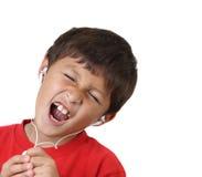 男孩耳机唱歌 库存照片