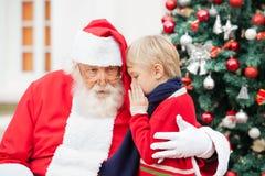 男孩耳语在圣诞老人的耳朵 免版税库存照片