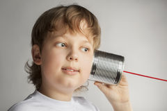 男孩能听电话锡 库存照片