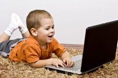 男孩膝上型计算机丝毫工作 库存图片