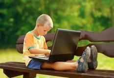 男孩膝上型计算机年轻人 免版税库存图片