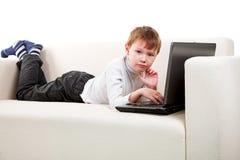男孩膝上型计算机 库存照片