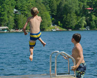 男孩船坞的俯冲轰炸到湖里 免版税库存图片