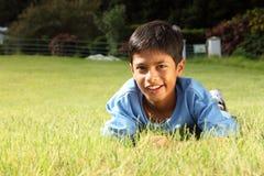 男孩草位于的公园微笑的年轻人 免版税库存图片